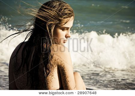 Thoughtful woman in the beach with sand in her skin.