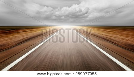 asphalt road through desert droughty area in cloudy day
