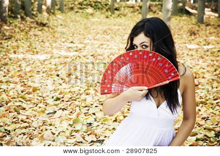Beautiful woman in a forest behind red fan