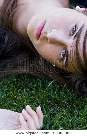 Green eyed laying woman staring at camera. Closeup view.