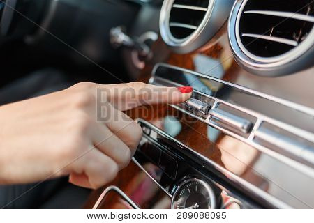 A Womans Hand Presses A Button In A Premium Car. Female Finger Presses The Button In The Car. The Co
