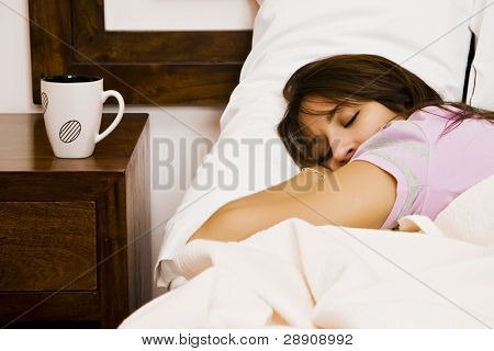 Jonge slapende vrouw in de buurt van lege cup