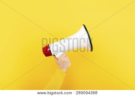Megaphone In Hand On A Yellow Background, Attention Concept Announcement