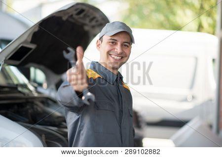 Smiling mechanic in front of a van