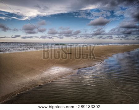 Water Reflection On The Sea Shore Landscape On The Sea Shore With Blue Sky Above.