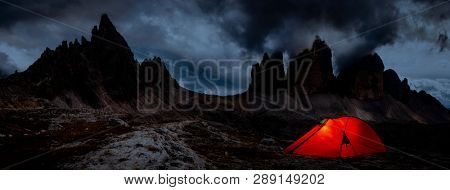 Night bivouac at Tre Cime di Lavaredo, milion star hotel under night sky, red illuminated tent on pass in Dolomites, Italy.