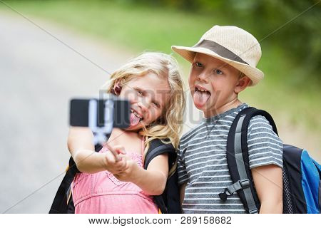 Siblings make selfie with the smartphone on the selfie stick and show tongue