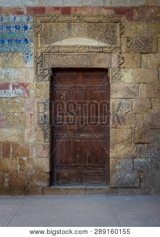 Cairo, Egypt - November 3 2018: Old Wooden Door Framed By Bricks Stone Wall At The Courtyard Of Al R