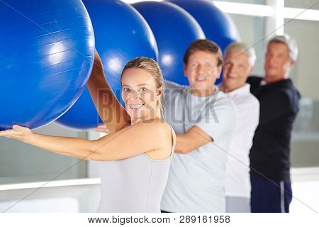 Group of seniors smiling while exercising in rehab center with gymnastics balls