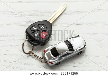 Car Keys With Remote Control Security And Car Key Chain On White Wooden Background.