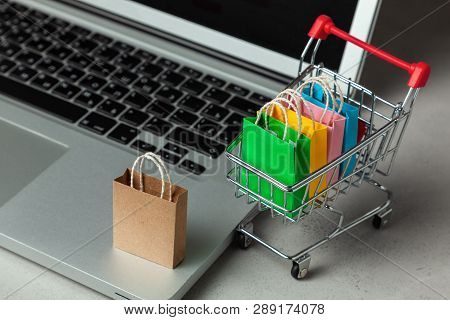 Buying Goods And Clothing In The Online Store. Shopping Bags In Shopping Cart On Laptop Keyboard.