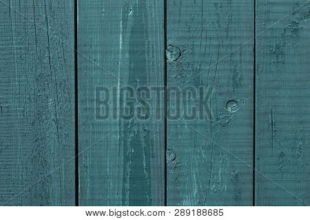 Gray-blue Wooden Fence Rough Wood. Wooden Fence Cracked Paint. Rough Wooden Boards Painted Gray-blue