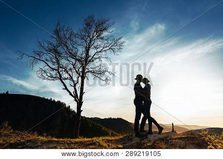 Silhouette Of A Couple In Love. Guy And Girl Hugging At Sunset. Couple Travels. Lovers In Nature. Ma