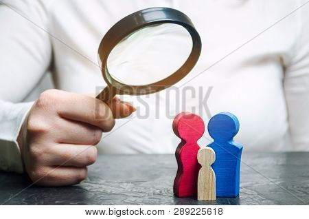 A Woman Is Holding A Magnifying Glass Over The Wooden Figures. Studying Family Composition, Needs An