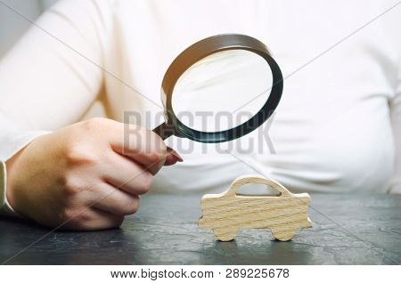 A Woman Holds A Magnifying Glass Over A Miniature Wooden Car. The Estimated Cost Of The Auto. Analys