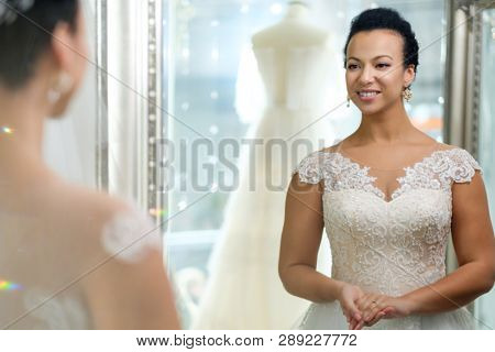 Beautifu bride choosing wedding dress in a wedding salon