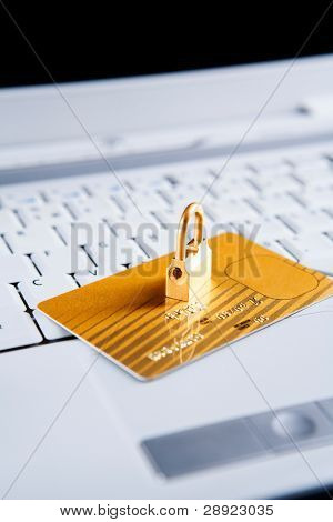 The golden lock in on top of the gold credit card on the laptop. All the important information from the card has been removed and modified. Focus mainly on front side of the lock.