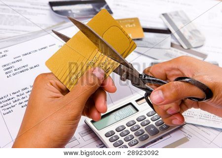 An action of cutting a credit card using a scissors.