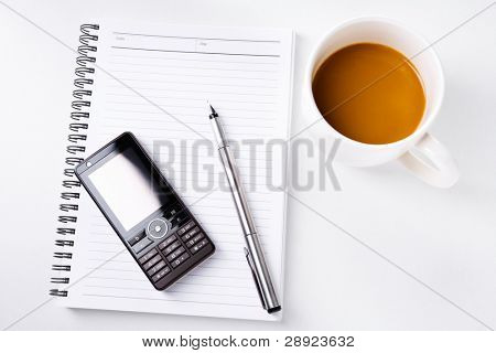 A still life image contains a cup of coffee and book with mobile phone and pen over it.