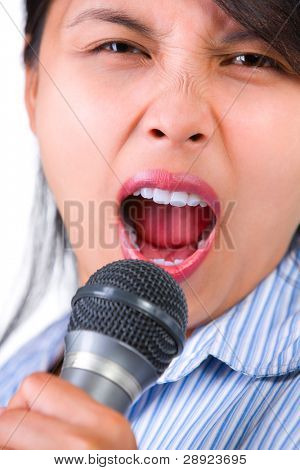 A woman is singing loudly using a microphone. Shallow depth of field, focus on the top lip.