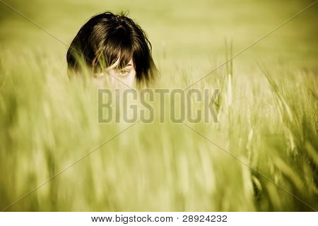 Young playful woman barely seen among the wheat