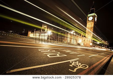 Nocturne scene with Big Ben behind light beams, angled composition.