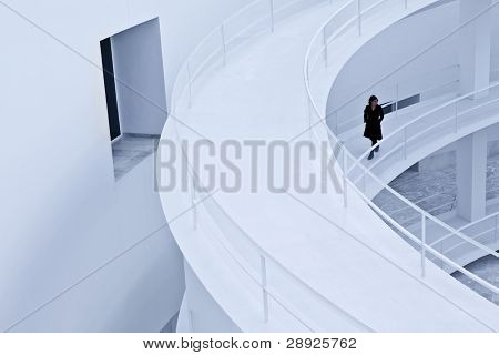 Woman in black walking over an abstract corridor