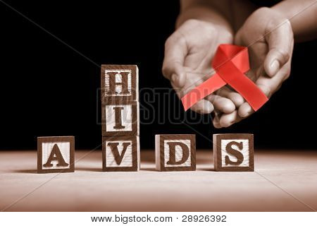 Hand holding red ribbon on back of HIV-AIDS letter blocks