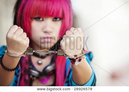 Young asian girl showing handcuffs on her wrists
