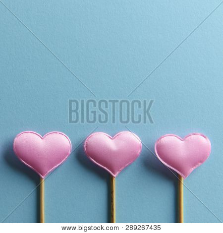 Three pink textile hearts on wooden sticks on blue background. Valentines day background, creative texture and love concept