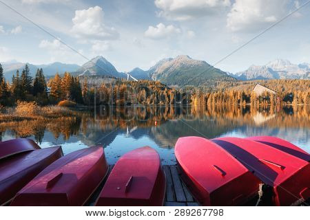 Picturesque autumn landscape with row of red wooden boats and high mountains on background. Strbske pleso lake in High Tatras National Park, Slovakia