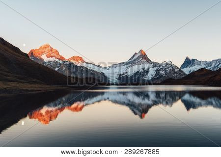 Bachalpsee lake with reflection in Swiss Alps mountains. Glowing snowy peaks on background. Grindelwald valley, Switzerland. Landscape photography