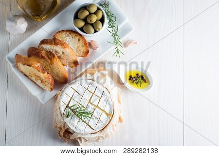 Baked Camembert Cheese. Fresh Brie Cheese And A Slice On A Wooden Board With Nuts, Honey, Rosemary,