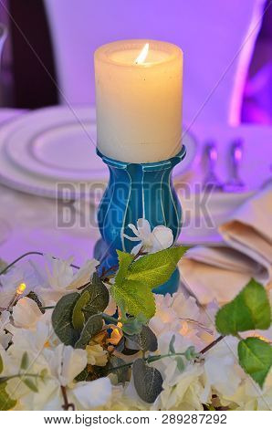 Table setup closeup with candle, plate, fork, knife and flowers poster