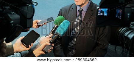 Abstract Man In A Suit And Tie Speaks To Reporters And Video Cameras. Female Hands Hold Microphones,