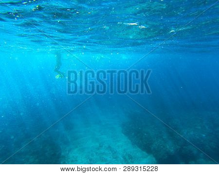 Tropical Sea Water Landscape With Coral Reef And Snorkel In Fins. Shallow Sea Water With Sun Beams.