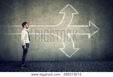 Confident Businessman Looking Into The Future As A Crossroad Arrows Split In Three Different Ways. C