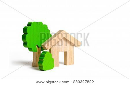 Wooden House And Trees. Environmentally Friendly And Environmentally Friendly Home. Modern Technolog