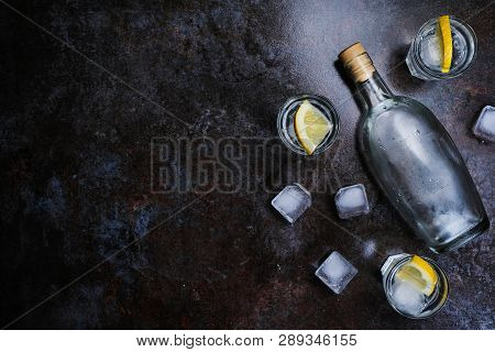 Cold Vodka In Shot Glasses With Lemon On Stone Background. Top View, Copy Space.