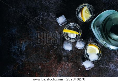 Vodka In Glasses With Lemon And Ice. On The Black Stone Table. Copyspace.