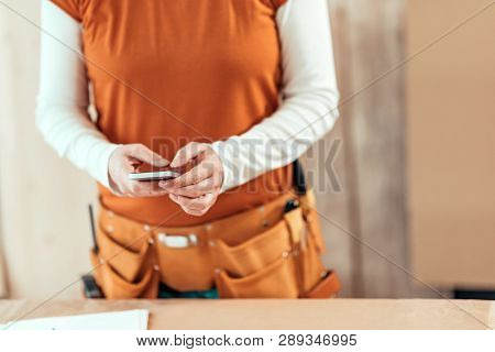 Female Carpenter Is Using Mobile Phone For Text Messaging, Close Up Of Hands Typing Sms On Smartphon