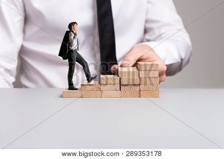 Confident Businessman With Jacket Over His Shoulder Walking Up The Stairs Made Of Wooden Pegs With H