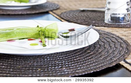 Table setting with white plate and silverware in a little green bag
