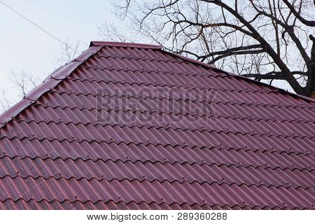 Part Of The Roof Of A Building With Red Tiles On A Background Of Gray Sky And Tree Branches