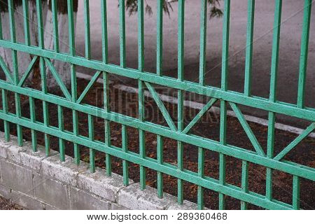 Part Of A Metal Fence Of Green Iron Rods In A Pattern