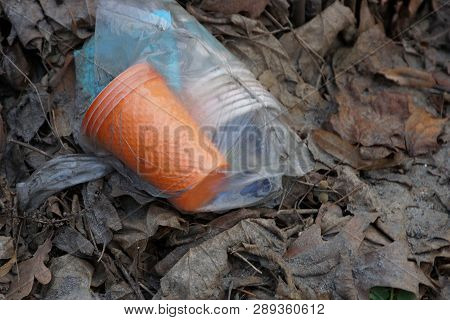 A Bag Of Trash Is Lying On Dry Leaves Outside