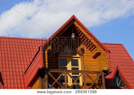 One Open Brown Wooden Balcony With Door And Red Tiles On The Roof Against The Sky
