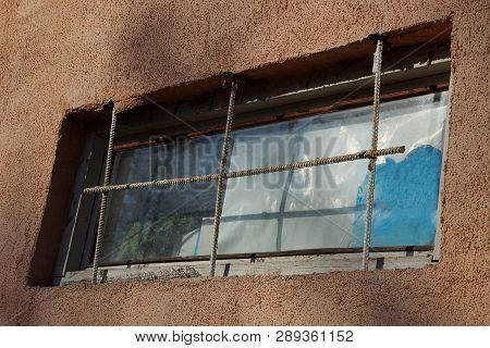 Old Window With Rusty Bars On A Brown Wall