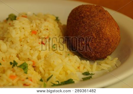 Yellow Rice And Fried Cutlet On A White Plate