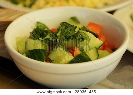 Salad Of Green Cucumbers And Red Tomatoes In A White Plate On The Table
